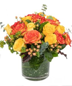 fall-colored roses and accents designed in a low cylinder vase with a leaf wrap