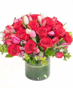 """P.S. I Love You - Tell someone, """"I love you!"""" with two of nature's most beautiful flowers, combined into one spectacular bouquet. Our P.S. I Love You flower bouquet features fragrant crimson roses for romance, and delicate pink tulips to signify friendship and devotion. Accented with a big pink bow, this magnificent floral gift will create a sensation. Approximately 14"""" (W) x 13"""" (H)"""